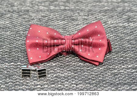 Wedding groom accessiries details. Red bow tie and black cuff-links