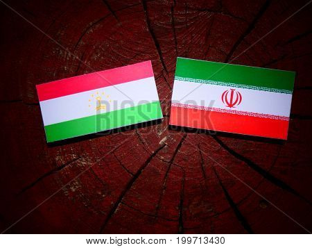 Tajikistan Flag With Iranian Flag On A Tree Stump Isolated