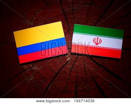 Colombian Flag With Iranian Flag On A Tree Stump Isolated