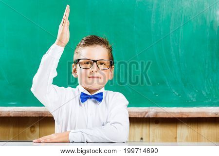 Happy pupil in white shirt and bow raising hand against chalkboard in school. Back to school concept background