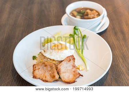 Fried rice with grilled pork and fried egg served with bak kut teh soup