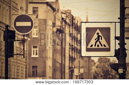 the street sign or the road sign the crosswalk and the movement it is forbidden on the city street in the photo with effect sepia