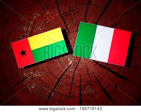 Guinea Bissau Flag With Italian Flag On A Tree Stump Isolated