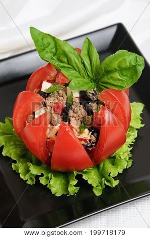 Festive appetizer. Tomato stuffed with chopped tuna salad egg tomato cubes olive slices and the addition of capers greens
