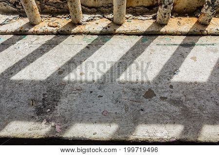 Shadow shining through the bars of the old prison used for detention.