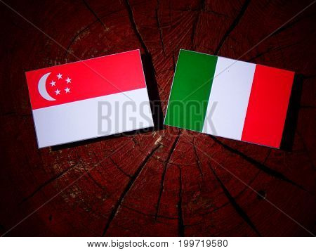 Singaporean Flag With Italian Flag On A Tree Stump Isolated