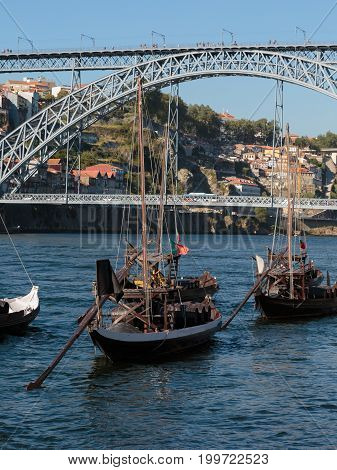 Traditional Rabelo Boats on the Bank of the River Douro and Dom Luis I Bridge in background - Porto Portugal