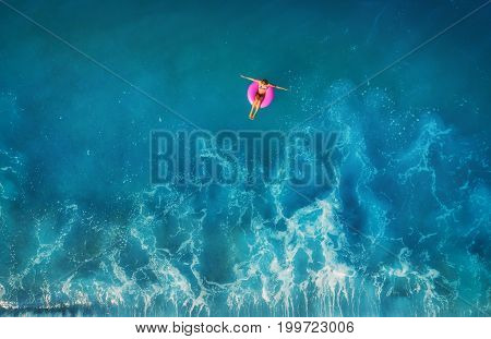 Aerial view of young woman swimming on the pink swim ring in the transparent turquoise sea in Oludeniz, Turkey. Summer seascape with girl, beautiful waves, blue water in sunny day. Top view from drone