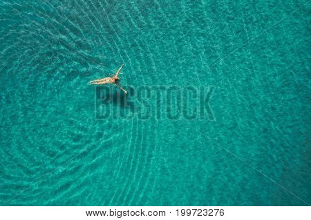 Aerial view of swimming woman in Blue Lagoon. Mediterranean sea in Oludeniz, Turkey. Summer seascape with girl, clear azure water, waves at sunrise. Transparent water.Top view from flying drone.Travel