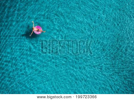 Aerial view of young woman swimming on the pink swim ring in the transparent turquoise sea in Blue Lagoon in Oludeniz, Turkey. Summer seascape with girl, azure water in the morning. Top view from drone
