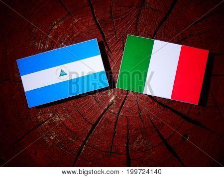 Nicaraguan Flag With Italian Flag On A Tree Stump Isolated
