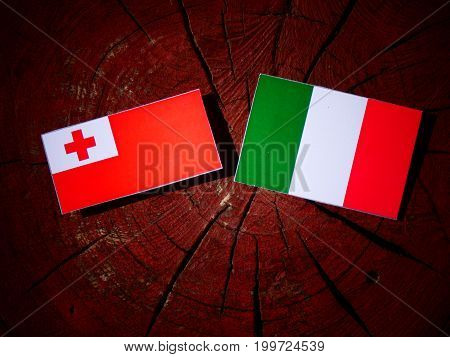 Tonga Flag With Italian Flag On A Tree Stump Isolated