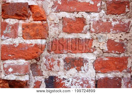 Old brick wall. The facade of the building. The crumbling wall of bricks. Wall texture background. The plaster on the wall. Uneven wall surface. The paint on the wall. Plastered walls. Abstract background. Painted brick wall
