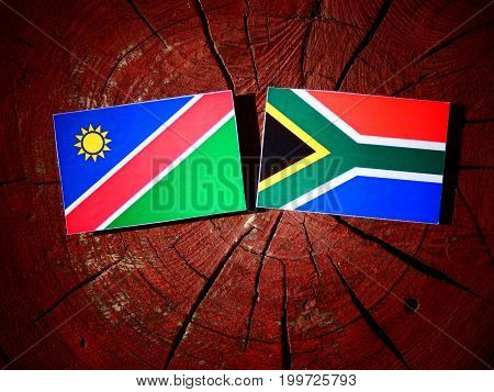 Namibian Flag With South African Flag On A Tree Stump Isolated