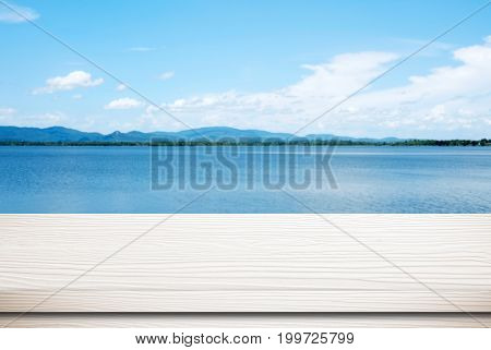 Empty white wood table over blur blue sea and sky background nature background spring and summer tropical climate travel concept for product display montage