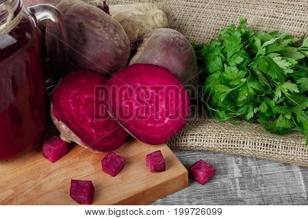 Close-up of a healthful composition of whole and sliced beetroots, ginger, and parsley on a light fabric and wooden background. A mason jar full of red drink near the vegetables on a cutting board.