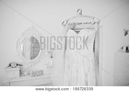 Beautiful Wedding Dress Hanging On The Rack In The Middle Of Big White Room. Black And White Photo.