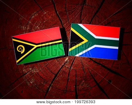 Vanuatu Flag With South African Flag On A Tree Stump Isolated