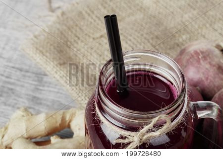 A op view of a beetroots juice in a mason jar with black straw on a bag and on a gray background. Beets and ginger near the beverage, close-up. Vegetables and drinks for healthy breakfast.