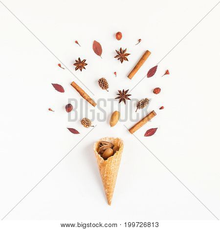 Autumn composition. Cinnamon sticks anise star pine cones autumn leaves in waffle cone. Flat lay top view square