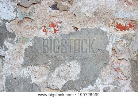 Gray grungy ruined wall. Old brick wall. The crumbling wall of bricks. Wall texture background. The plaster on the wall. Uneven wall surface. The paint on the wall. Plastered walls. Abstract background. Painted brick wall