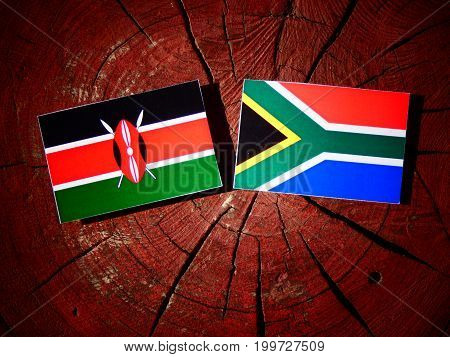 Kenyan Flag With South African Flag On A Tree Stump Isolated