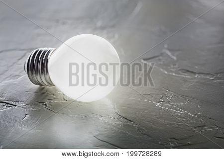 White light bulb glowing on concrete background idea concept