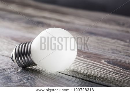 White light bulb glowing on wooden background idea concept