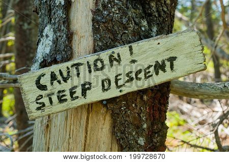 caution steep descent warning sign on a tree
