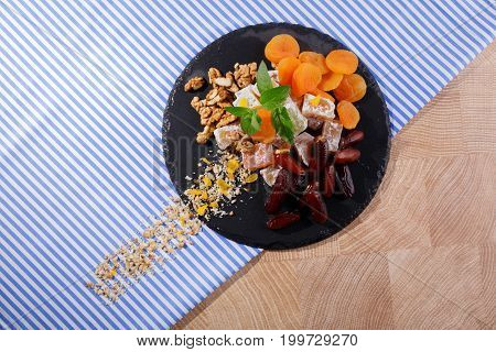 A top view of a black plate full of yummies and fruits on a colorful fabric background. Sugary turkish delight with red date fruits, aromatic mint, dried apricots and crunchy walnuts. Copy space.