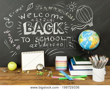Back to school concept with writing on blackboard and desk apple books stationery