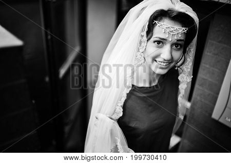 Portrait Of A Beautiful Bride Wearing Casual Clothes And Veil Walks Out Of The Room. Black And White