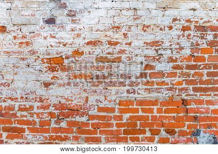old brick wall of the house with the remains of white paint. grunge textured background