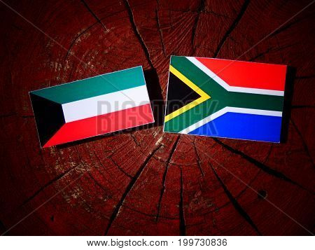 Kuwaiti Flag With South African Flag On A Tree Stump Isolated