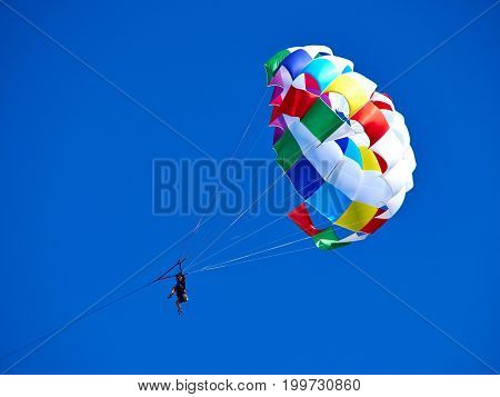 Parasailing with colorful parachute in clear blue sky popular vacation activity in summer resorts