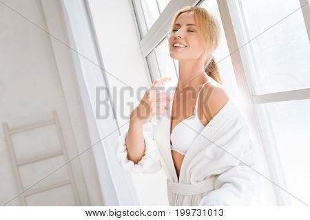 Moment of pleasure. Delighted woman keeping eyes closed while smiling and dispersing spray on neck
