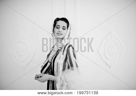 Portrait Of Bride Posing With Her Long Veil In The Big White Room. Black And White Photo.