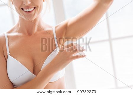 Hygiene. Attractive female person keeping smile on her face and raising arm while refreshing her skin under arms