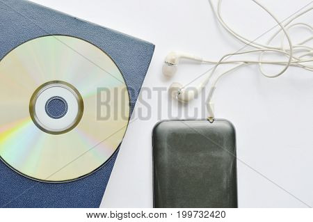 book and earphones connect in smartphone on white background