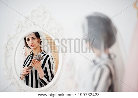 Portrait Of A Fantastic Bride Posing With Lavender Flowers In The Mirror.