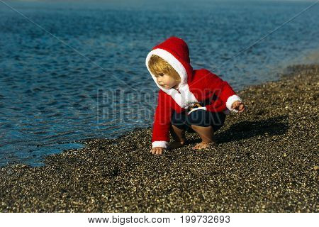 Boy in santa claus costume playing with pebbles on beach on sunny summer day on blue sea background. Christmas and new year. Holidays celebration concept. Child and childhood