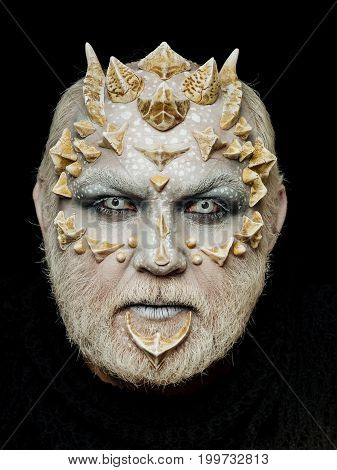 Alien or reptilian makeup. Demon head on black background. Man with dragon skin and beard. Horror and fantasy concept. Monster face with white eyes sharp thorns and warts.