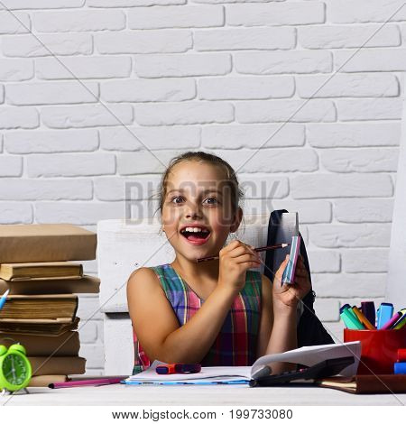 Girl Sits At Desk With Near Books Stack And Globe