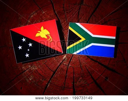 Papua New Guinea Flag With South African Flag On A Tree Stump Isolated