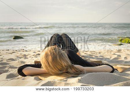 blond beautiful woman lying at sunny sea beach relaxing