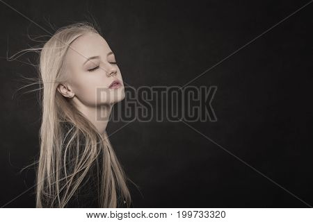 beautiful sensual blond girl on black background on black background with copy space