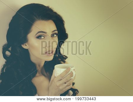 Beauty salon and fashion. Girl with fashionable makeup. Woman has stylish long hair drink tea or coffee from cup. Cosmetics and skincare. Hairdresser and barber.