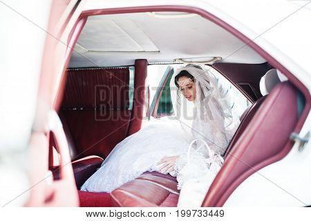 Flawless bride sitting in wedding car at salon