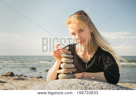 beautiful woman stacking stones on rock at sunny sea beach