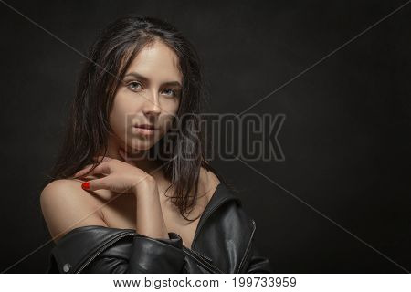 beautiful woman with bare shoulders looking at camera on black background